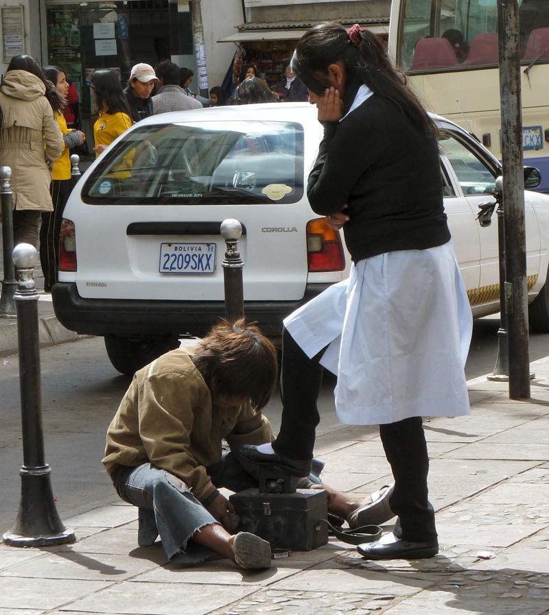 13 heures, sortie des classes. Les enfants de la bourgeoisie locale issus de collèges privés aux uniformes distinctifs se font cirer les chaussures par d'autres enfants, véritables gamins des rues pour qui l'école semble être inaccessible (la scolarité est pourtant obligatoire jusqu'à 16 ans)